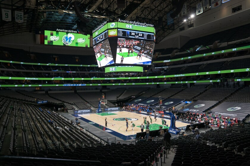 The Orlando Magic and the Dallas Mavericks play in an otherwise empty American Airlines Center in Dallas.