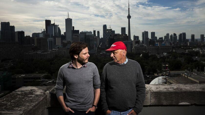 TORONTO, CANADA -- SEPTEMBER 9, 2013--Actor Daniel Bruhl, left, is photographed along side race car