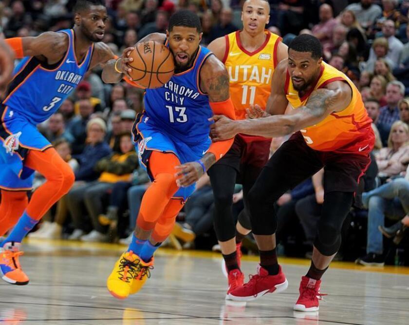 Derrick Favors (d) de Utah Jazz comete una falta sobre Paul George (c) de Oklahoma City Thunder durante un partido de la NBA disputado este lunes en el Vivint Smart Home Arena de Salt Lake City, Utah (EE.UU.). EFE