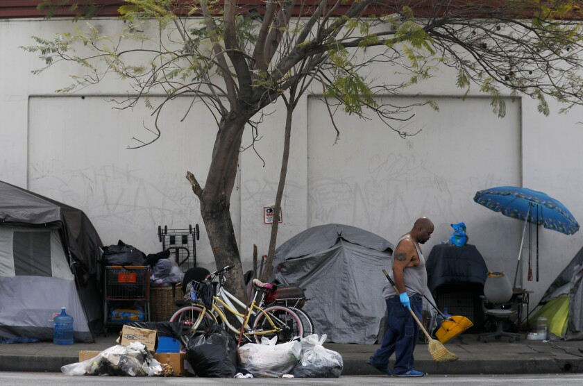 Duanne Hardaway clears the street in front of tents on Broadway Place in L.A.