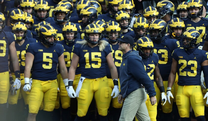 Michigan coach Jim Harbaugh walks in front of his players before a game against Penn State in November.