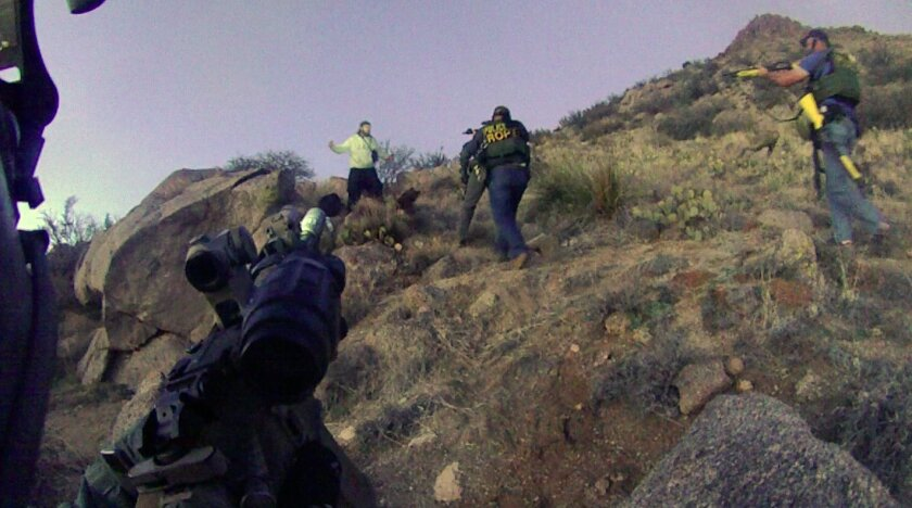 This March 16, 2014 photo of an Albuquerque Police Department lapel camera still, shows a standoff with an illegal camper in the Albuquerque foothills, before firing six shots at the man. Police say James Boyd, 38, refused to drop a knife and had threatened to kill officers. He later died at a near