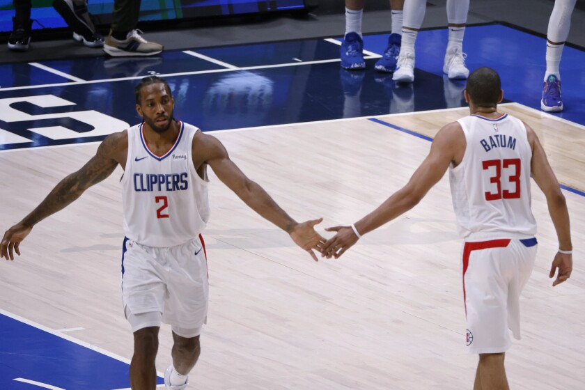 Los Angeles Clippers forward Nicolas Batum (33) congratulates forward Kawhi Leonard (2) after Leonard made a 3-point basket against the Dallas Mavericks in the second half during Game 6 of an NBA basketball first-round playoff series in Dallas, Friday, June 4, 2021. (AP Photo/Michael Ainsworth)