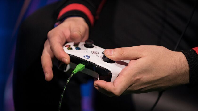 A gamer holds an Xbox controller.