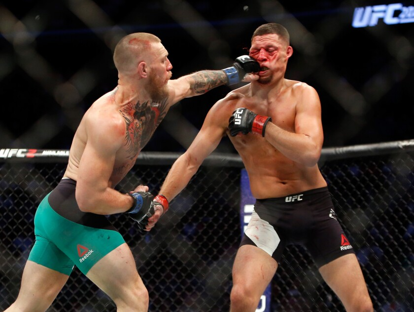Conor McGregor lands a left to the face of Nate Diaz during their welterweight rematch at UFC 202.