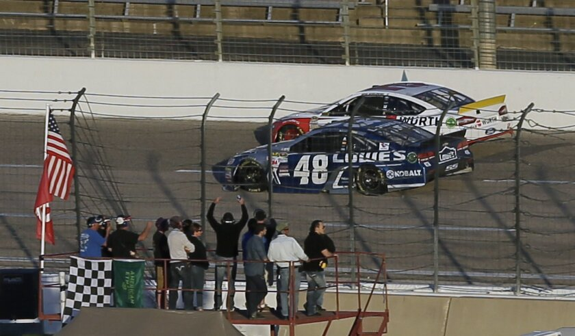 Jimmie Johnson (48) passes Brad Keselowski (2) taking the lead in the closing laps of the NASCAR Sprint Cup Series auto race at Texas Motor Speedway in Fort Worth, Texas, Sunday, Nov. 8, 2015. (AP Photo/Tim Sharp)