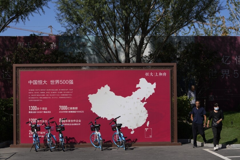 People walk by a map showing Evergrande development projects in China at an Evergrande new housing development in Beijing, Wednesday, Sept. 22, 2021. The Chinese real estate developer whose struggle to avoid defaulting on billions of dollars of debt has rattled global markets announced Wednesday it will make a closely watched interest payment due this week, while the government was silent on whether it might intervene. (AP Photo/Andy Wong)
