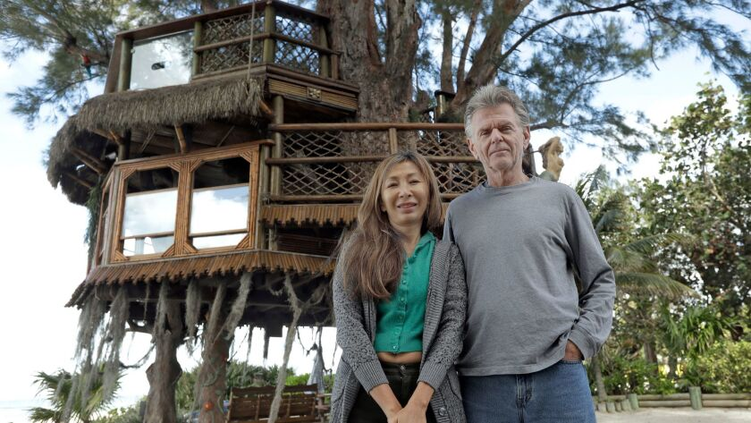 Lynn Tran and her husband, Richard Hazen, pose near their Australian pine treehouse Jan. 4 in Holmes Beach, Fla. The couple is hoping the U.S. Supreme Court will hear their case after city and state officials ordered the treehouse removed.