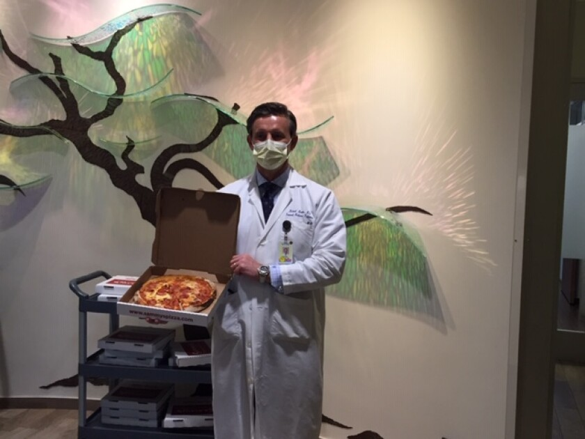 Dr. Michael Martin, internal medicine at Sharp Rees-Stealy Medical Group, is ready to dig into his pizza.