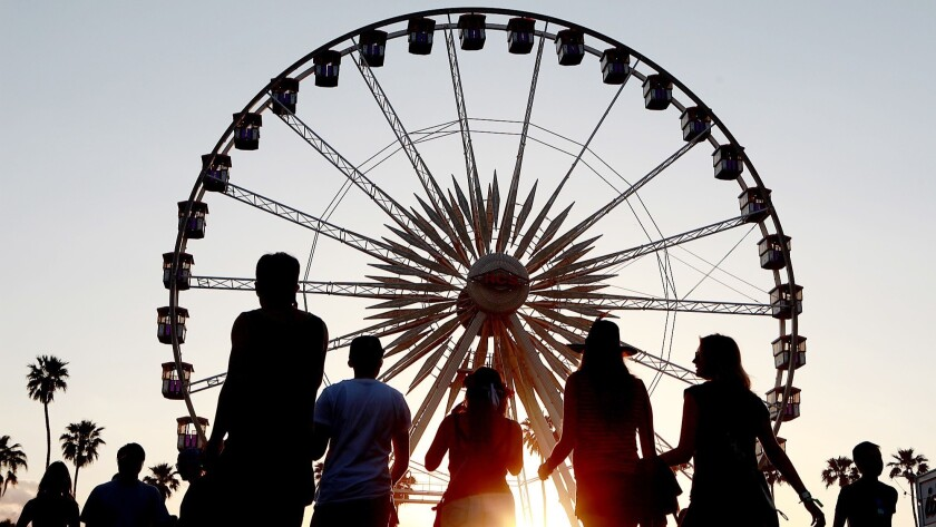 INDIO, CA - APRIL 12, 2013: The sun sets on festival goers and the ferris wheel at the Coachella Mus