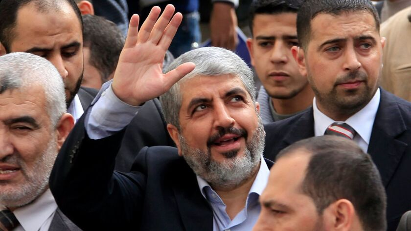 Exiled Hamas leader Khaled Meshaal waves to Palestinian students during a visit to the Islamic Unive
