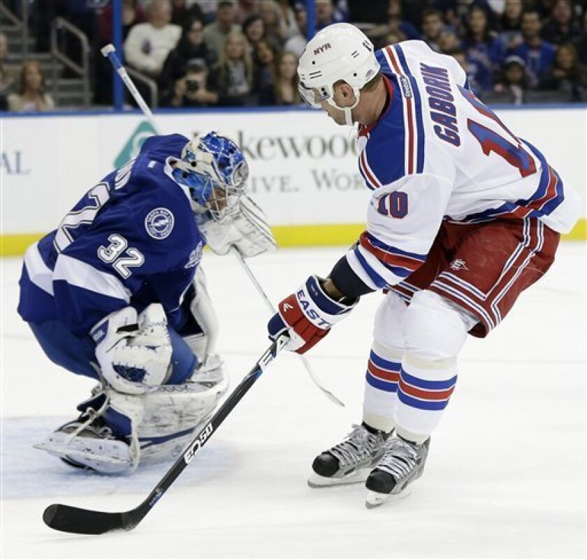 Tampa Bay Lightning goalie Mathieu Garon (32) makes a save on a breakaway by New York Rangers right wing Marian Gaborik (10), of Slovakia, during the first period of an NHL hockey game on Saturday, Feb. 2, 2013, in Tampa, Fla. (AP Photo/Chris O'Meara)