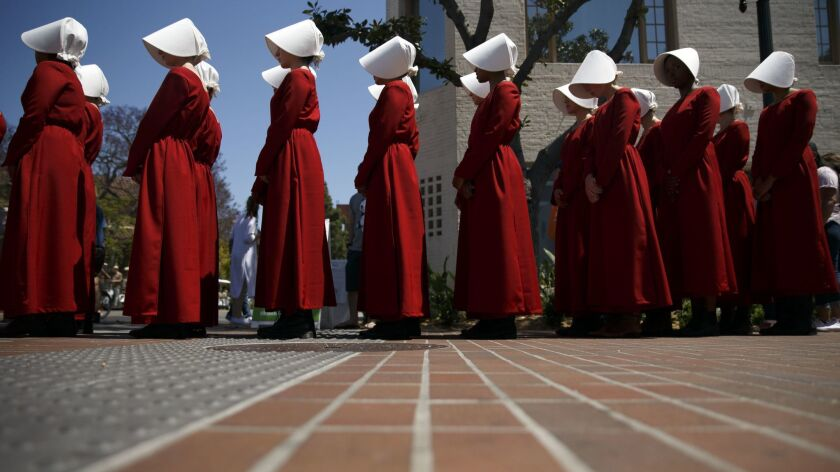 Actresses from the Hulu series The Handmaid's Tale, based on the book by Margaret Atwood, stand in a