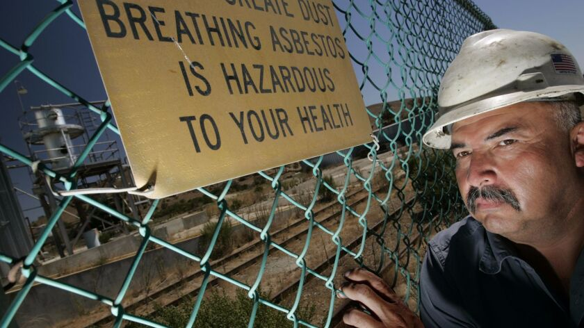 Manuel Zuniga stands outside the fence of the KCAC asbestos processing plant off Highway 101 south of King City, Calif.