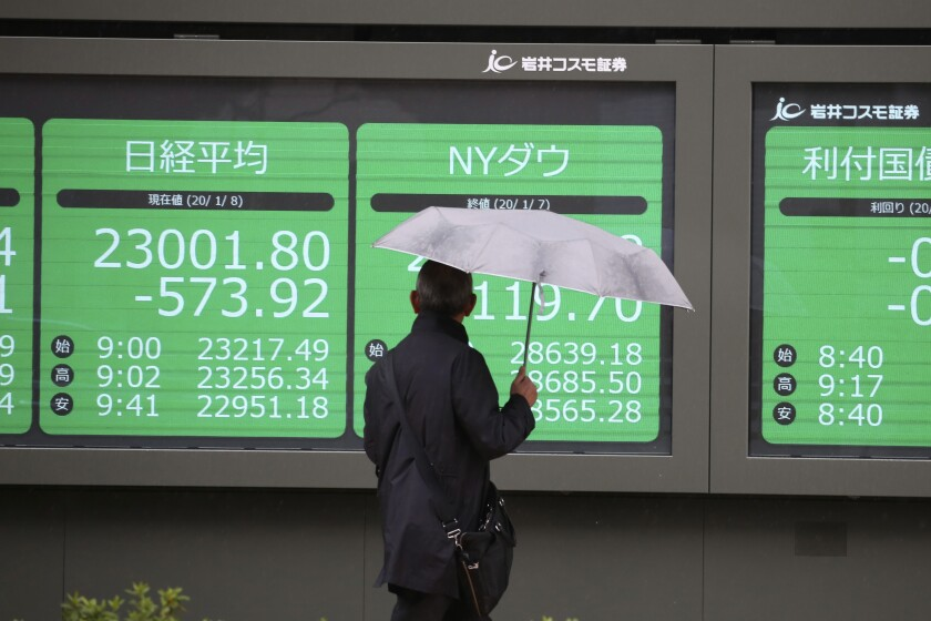 A man pauses at a security firm's electronic stock board Jan. 8 in Tokyo.