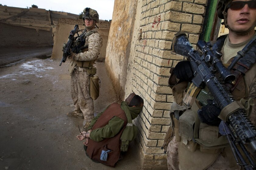 Cpl. Jason Gaal (left) and Lance Cpl. Derek Goins (right) guard their prisoner as the rest of the squad positions themselves inside for safety. The prisoner was identified by Gall and Staff Sgt. Nathan Stocking as the man who the day before tried to detonate an IED.