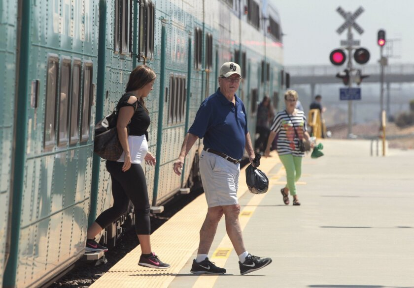 Passengers exit a northbound Coaster train at the Poinsettia train station in Carlsbad on Wednesday. Service throughout coastal San Diego County will be suspended on four upcoming weekends for track maintenance work.