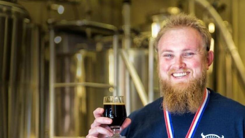 Kris Ketcham holding a Witty Moron beer. The beer won the gold medal at the 2014 Great American Beer Festival. (/ Courtesy photo)