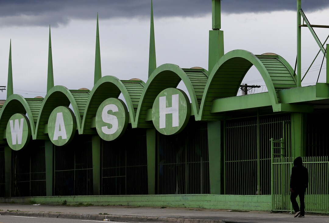 A man walks past a shuttered car wash along Manchester Avenue in South L.A., where the sign serves as a reminder for what to do during the coronavirus pandemic.
