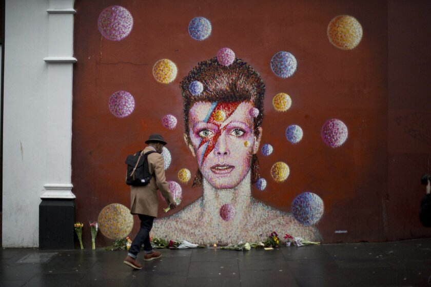 "A man walks to place flowers alongside other tributes beside a mural of British singer David Bowie by artist Jimmy C in Brixton, south London, Monday, Jan. 11, 2016. David Bowie, the iconic and shape-shifting British singer whose illustrious career lasted five decade with hits like ""Fame,"" ''Heroes"