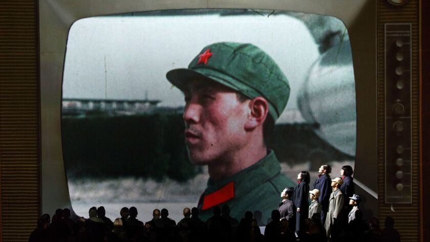 Actors as Chinese communists perform with the LA Philharmonic as a large projection screen shows TV