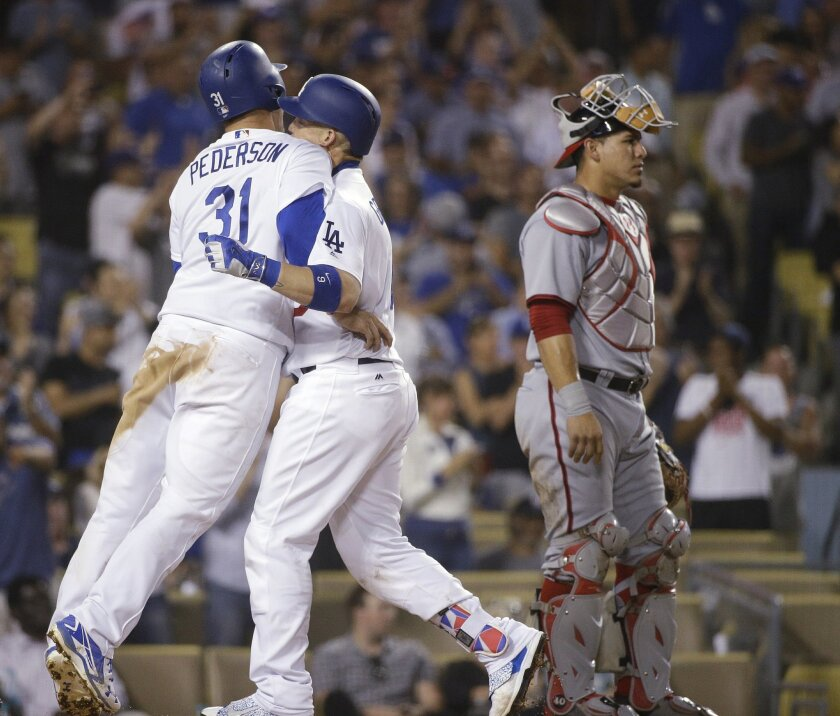 Los Angeles Dodgers' Yasmani Grandal, center, celebrates his three-run home run with Joc Pederson as Washington Nationals catcher Wilson Ramos, right, stands nearby during the eighth inning of a baseball game Tuesday, June 21, 2016, in Los Angeles. The Dodgers won 3-2. (AP Photo/Jae C. Hong)