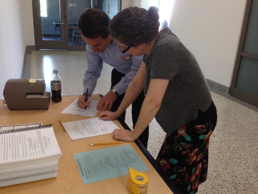 Campaign spokesman Craig Benedetto goes over referendum forms with City Clerk Elizabeth Maland.
