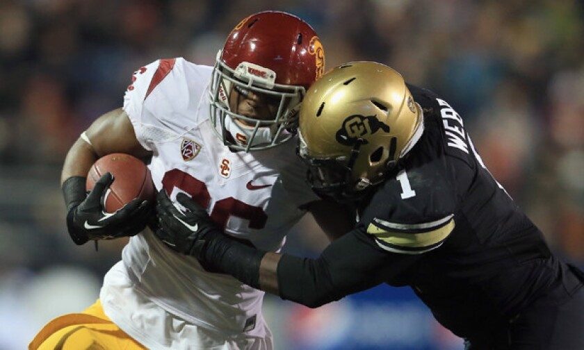 USC tight end Xavier Grimble, left, battles Colorado linebacker Derrick Webb on a catch during a game in November. Grimble says he will make himself available for the NFL draft.