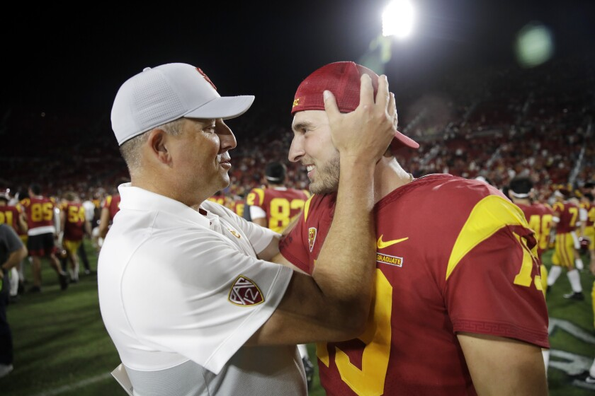 USC coach Clay Helton celebrates with quarterback Matt Fink after the team's 30-23 win over Utah on Friday.