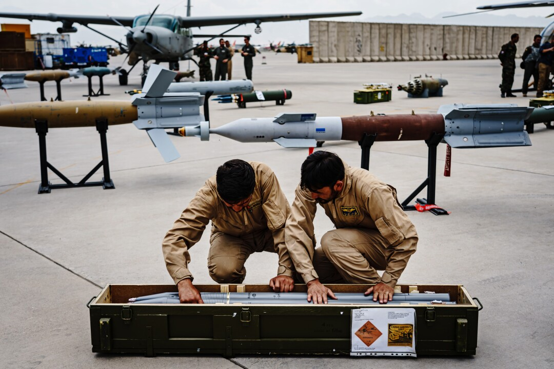 Two troops put weapons in a container.