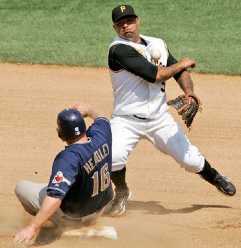 Pittsburgh Pirates second baseman Luis Rivas turns a seventh inning double play over Chase Headley (16) in Pittsburgh Sunday.