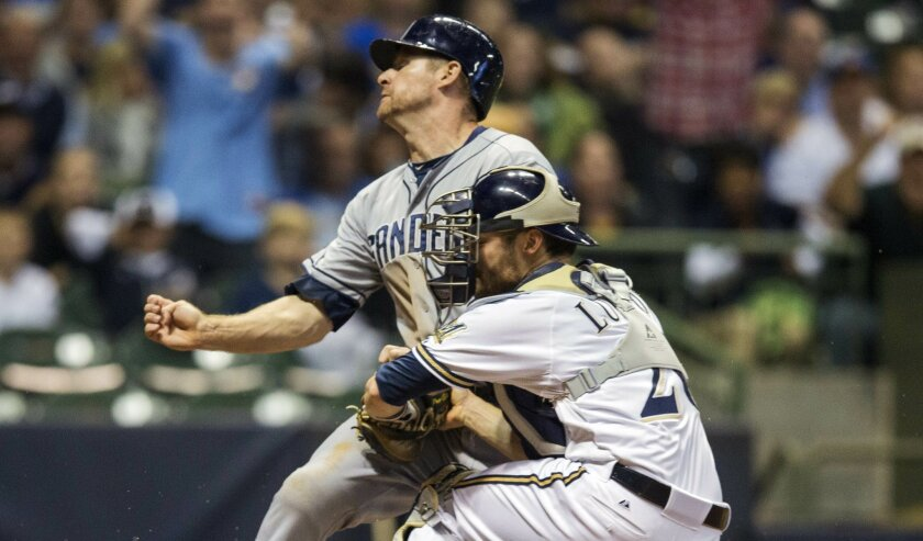 Chase Headley is safe at home despite a collision with Brewers catcher Jonathan Lucroy.