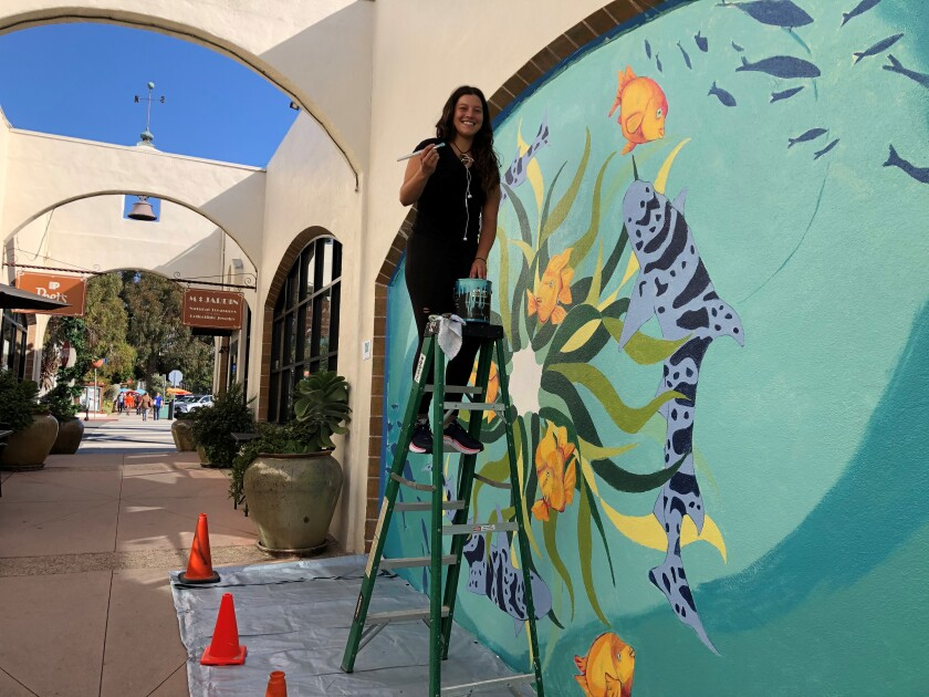 Melanie Atesalp works on her new sea-life mural on the Arcade Building on Wall Street in La Jolla.