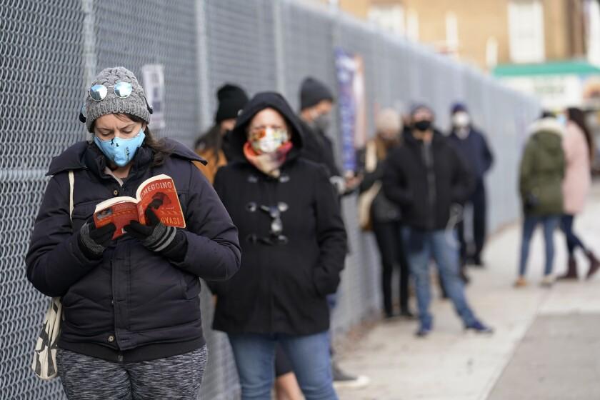Ashley Gannon, izquierda, lee mientras espera en fila en las afueras de un sitio de pruebas de coronavirus