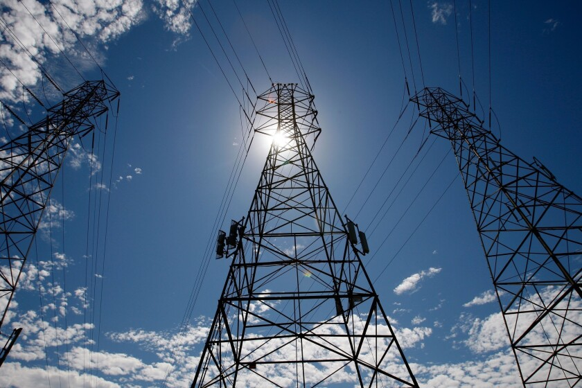 The sun shines over towers carrying electrical lines.