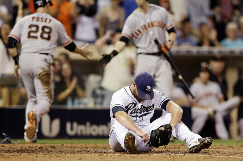 San Diego Padres closing pitcher Craig Kimbrel, front, sits after San Francisco Giants' Buster Posey (28) scored from third off a wild pitch during the ninth inning of a baseball game Wednesday, Sept. 23, 2015, in San Diego. Behind, Posey is greeted by teammate Trevor Brown. (AP Photo/Gregory Bull)