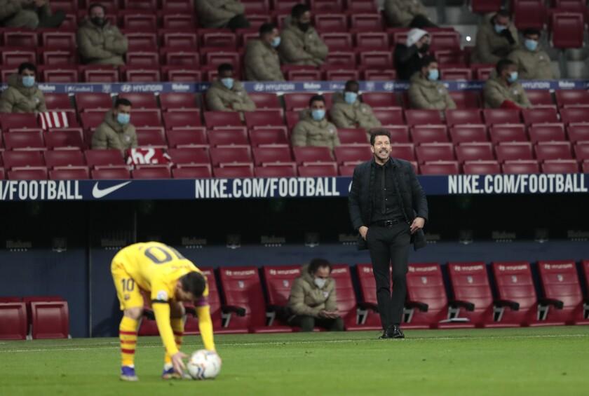El técnico Diego Simeone del Atlético de Madrid grita instrucciones mientras el delantero Lionel Messi se prepara para ejecutar un tiro libre en el partido por La Liga de España, el sábado 21 de noviembre de 2020, en Madrid. (AP Foto/Bernat Armangue)