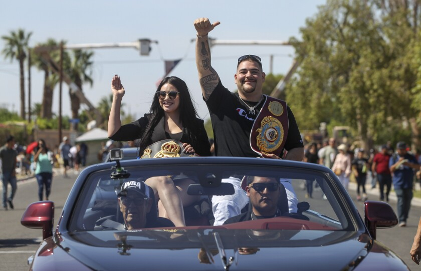 Andy Ruiz Jr. and his wife, Julie, ride in a parade Saturday in his hometown of Imperial. Ruiz beat Anthony Joshua on June 1 to become boxing's heavyweight champion of the world.