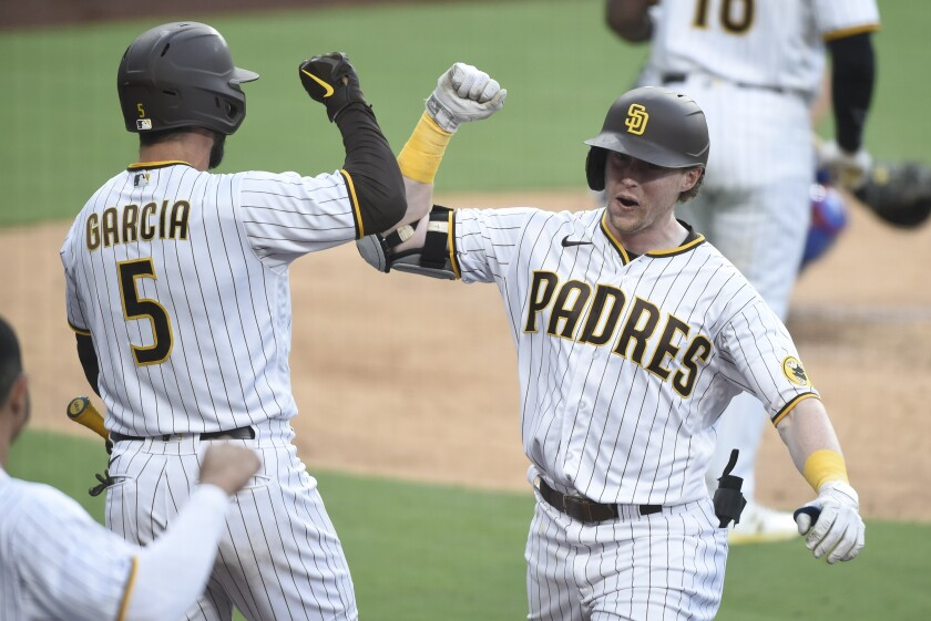 Jake Cronenworth #9 of the San Diego Padres is congratulated by Greg Garcia #5 after hitting a solo home run