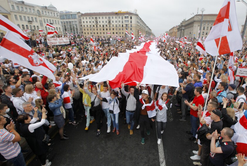 Demonstrators carry historical flags of Belarus as thousands gather for a protest at Independence Square in Minsk, Belarus