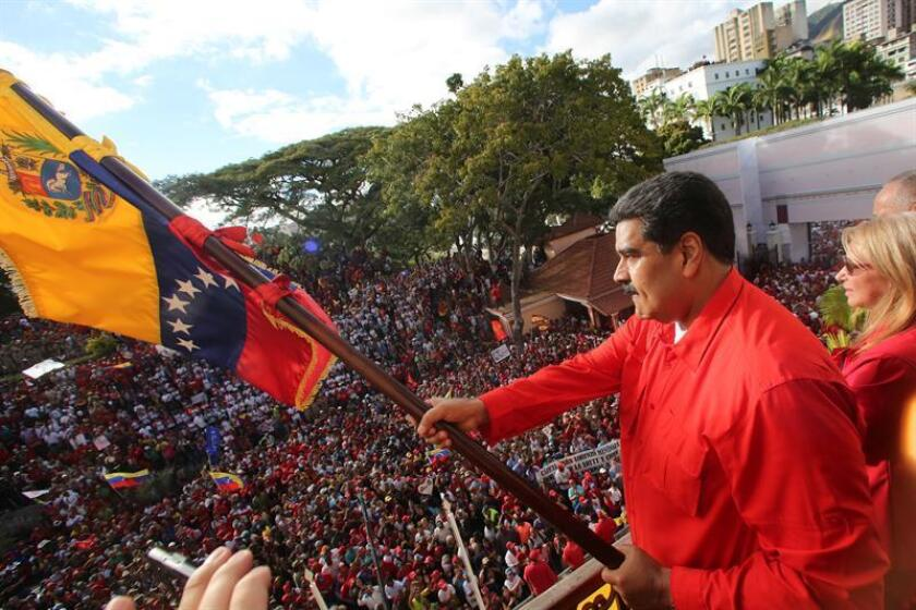 A handout photo made available by the Venezuelan presidency's Miraflores press office showing Venezuelan President Nicolas Maduro (C) waving the national flag as he gives a speech to supporters next to his wife Cilia Flores (R) outside the Miraflores Palace, in Caracas, Venezuela, on Jan. 23, 2019. EPA-EFE/Marcelo Garcia/Miraflores Press / HANDOUT