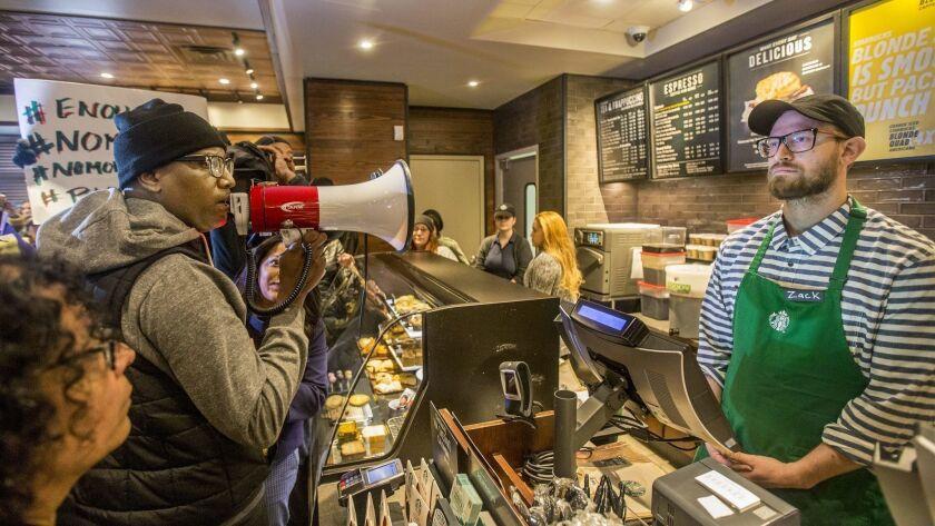 Local Black Lives Matter activist Asa Khalif, left, stands inside a Starbucks, Sunday April 15, 2018