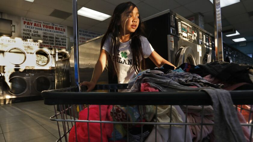 LONG BEACH, CALIFORNIA--MARCH 15, 2019--Isabella Kap, age 8, helps her grandmother at the laundromat