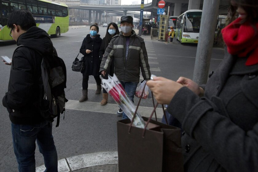 In this March 6, 2015 photo, residents wear masks for protection during a polluted day in Beijing. Since China launched a sweeping legal reform in January that toughens environmental penalties and allows more groups to sue polluters, Chinese have been rushing to test out the new laws and, in some c