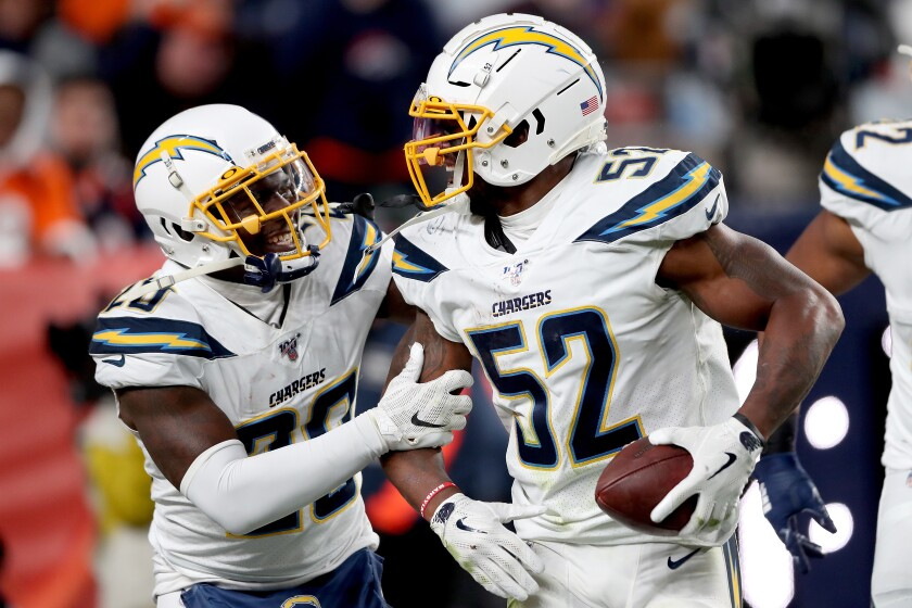 Chargers linebacker Denzel Perryman celebrates with Desmond King II after intercepting a pass during a game against the Broncos on Dec. 1.
