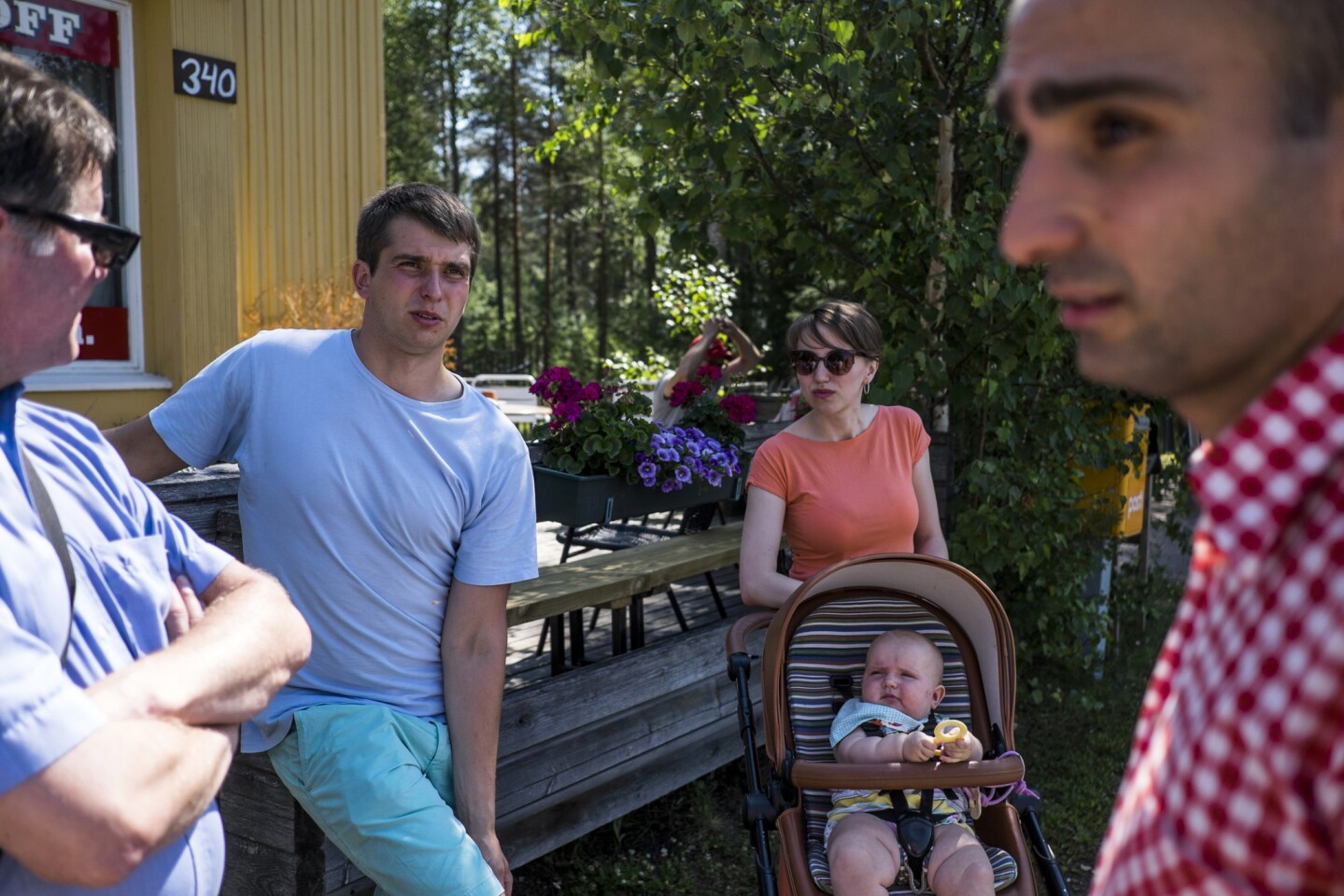 Sergei Kotelnikova, second from left, is shown with his wife, Anya, and their daughter, Emily, at a refugee center in Konnunsuo, Finland. The family fled Russia, as did Alin Tovmasian, right, after Jehovah's Witnesses were labeled extremists there and their faith was banned. At left is Harri Ikonen, a member of the Jehovah's Witnesses community in Konnunsuo.