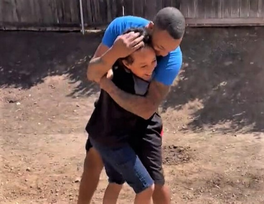J'Amore Morton and son, Aiden, 10, after Aiden discovered a basketball hoop in his back yard, thanks to dad.