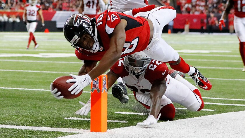 Falcons receiver Taylor Gabriel dives for the pylon past Cardinals defensive back Tony Jefferson to score a touchdown during the second half Sunday.