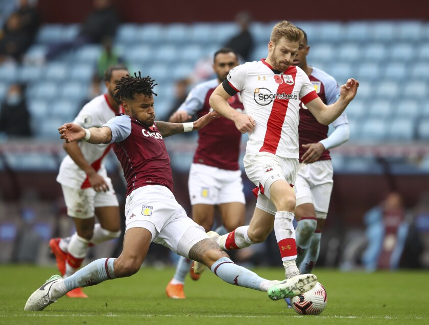 Aston Villa's Tyrone Mings, left slides in to tackle Southampton's Stuart Armstrong during the English Premier League soccer match between Aston Villa and Southampton at Villa Park in Birmingham, England, Sunday, Nov. 1, 2020. Southampton won the game 4-3. (Michael Steele/Pool via AP)