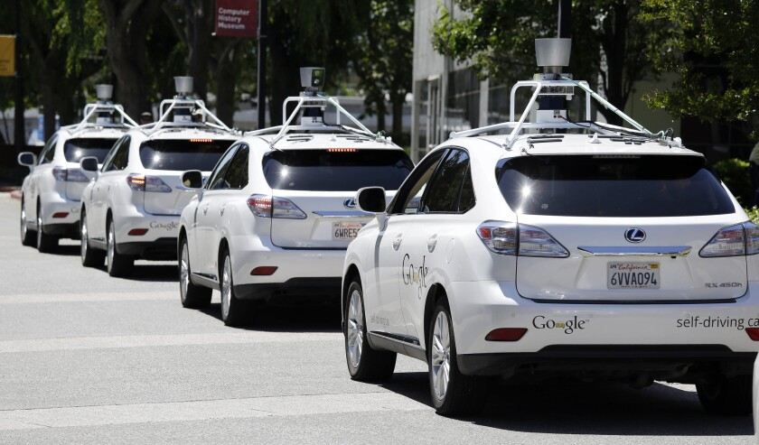 A row of Google self-driving Lexus cars are lined up at a Google event outside the Computer History Museum in Mountain View, Calif., on May 13, 2014.